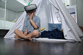 Young boy using virtual reality goggles in tent