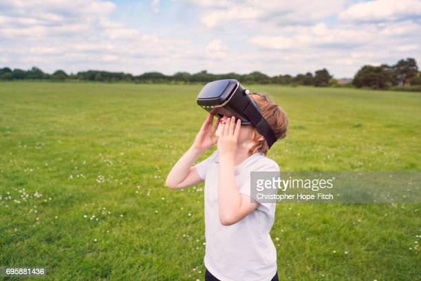 Young boy using VR headset in a field