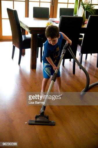 Young boy vacuuming : Foto de stock