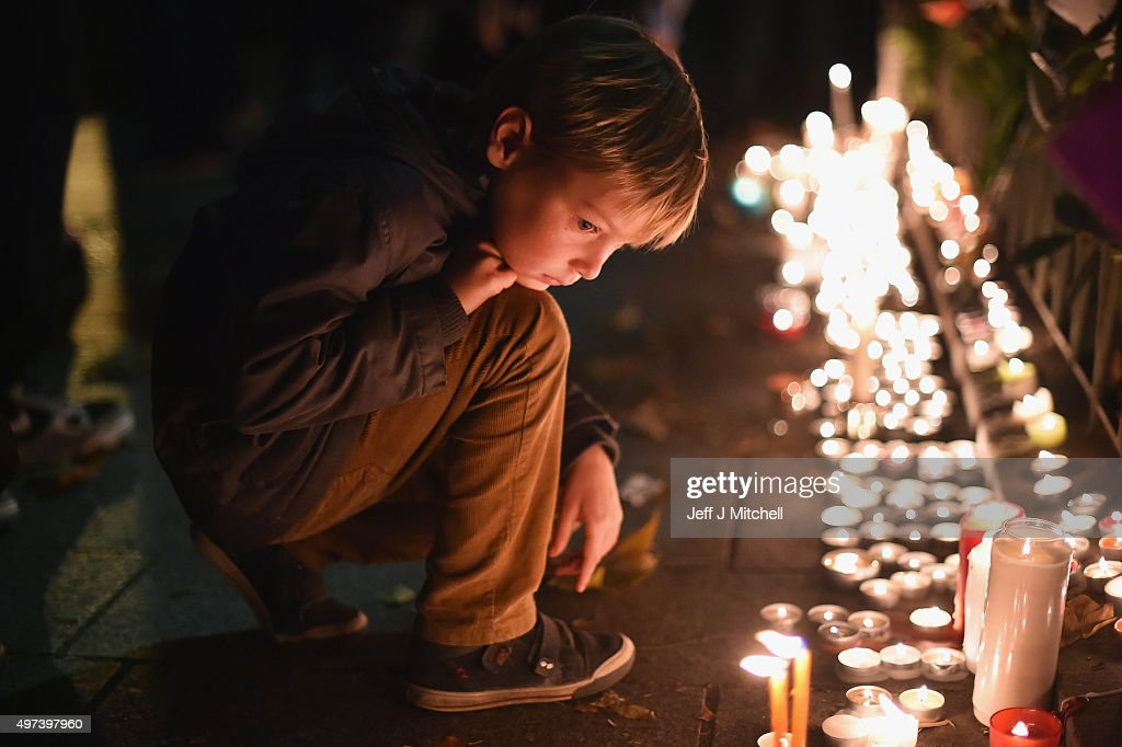 A young boy views tributes left opposite the main entrance of Bataclan concert hall as French police lift the cordon following Fridays terrorist...