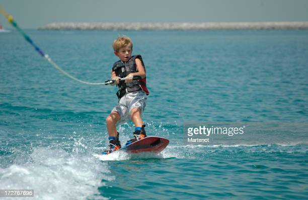 Young boy wake boarding on ocean
