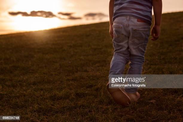 Young boy walking at sunset