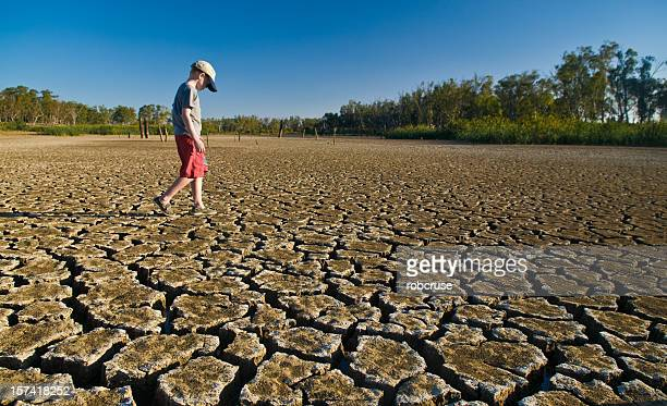 Young boy walking on a dry lake bed looking down