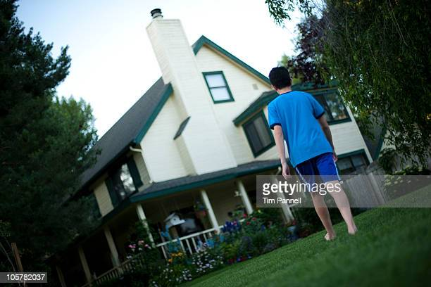 Young boy walking towards house