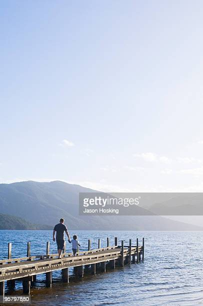 Young boy walking with his father on lake jetty