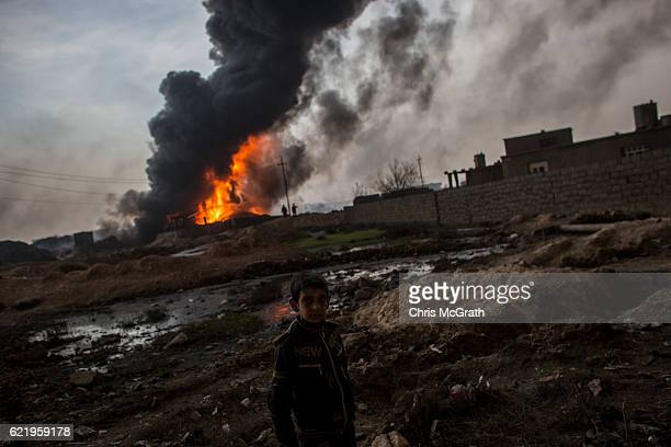 A young boy walks in front of a burning oile well set on fire by fleeing ISIS members on November 9 2016 in Al Qayyarah Iraq Many families have begun...