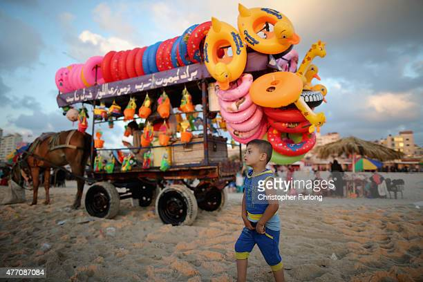 A young boy walks past a beach vendor selling colourful inflatable toys on Gaza beach on June 13 2015 in Gaza City Gaza Palestinians are taking the...