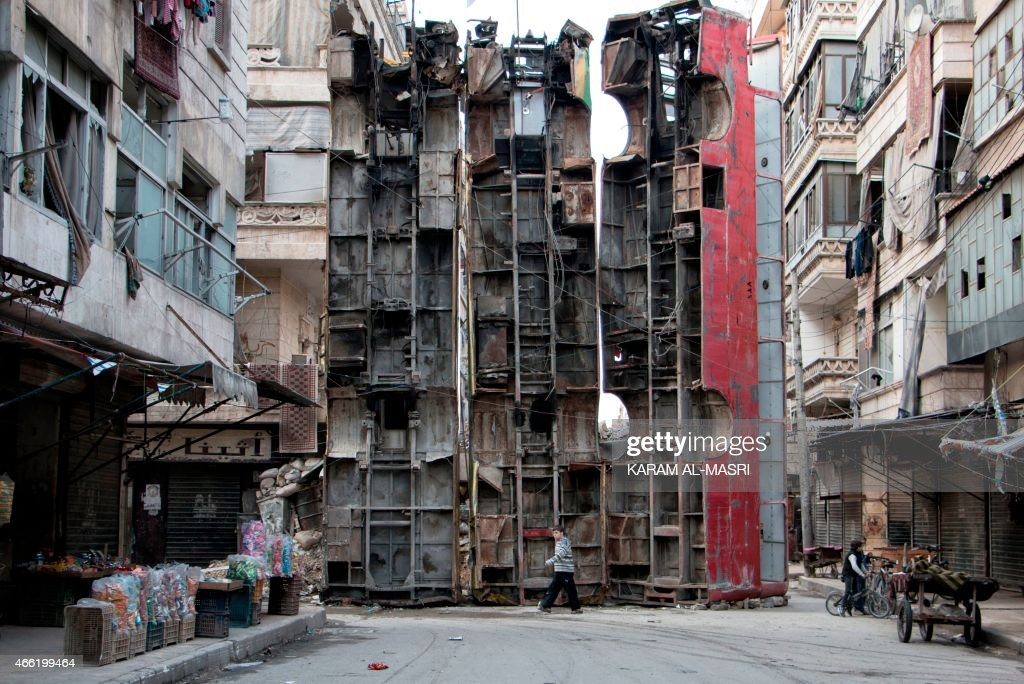 A young boy walks past a makeshift barricade made of wreckages of buses to obstruct the view of regime snipers and to keep people safe on March 14...
