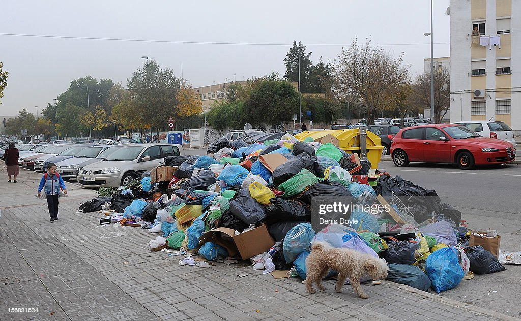 A young boy walks past a pile of uncollected garbage during the 21st day of the garbage collectors strike on November 22, 2012 in Jerez de la Frontera, Spain. The garbage collectors agreed on November 22nd to a compromise deal saving 123 job redundancies due to be cut in return for salary reductions.