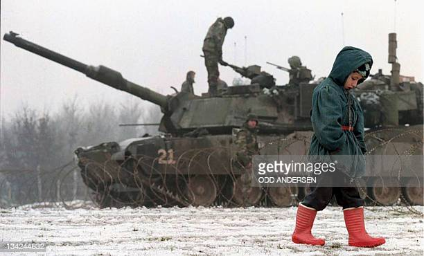 A young boy walks past January 1996 a makeshift US army base outside the northern Bosnian city of Tuzla AFP PHOTO ODD ANDERSEN