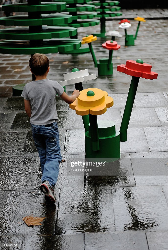 A young boy walks through a lifesized LEGO forest during a wet morning in Sydney on April 18 2012 to celebrate the 50th anniversary of the LEGO brick...