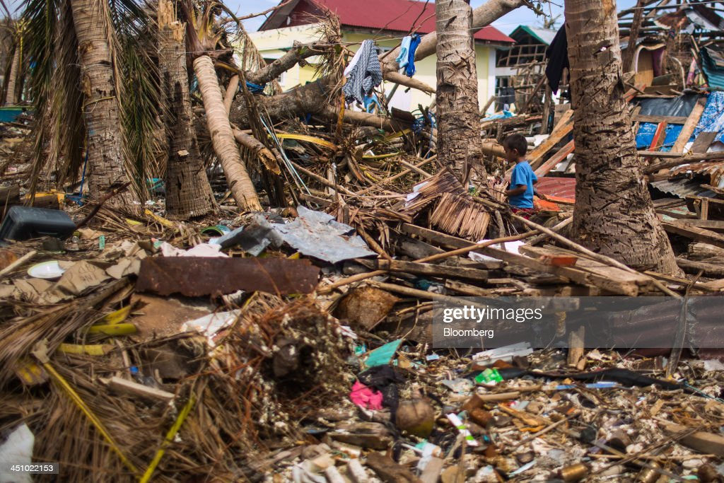 A young boy walks through debris in Sulyan Village in Eastern Samar, the Philippines, on Wednesday, Nov. 20, 2013. Super Typhoon Haiyan slammed into the central Philippines on Nov. 8, knocking down most buildings, killing thousands, displacing 4 million people and affecting more than 10 million. Photographer: Julian Abram Wainwright/Bloomberg via Getty Images