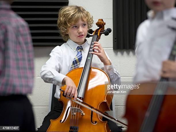 Young boy warming up his cello