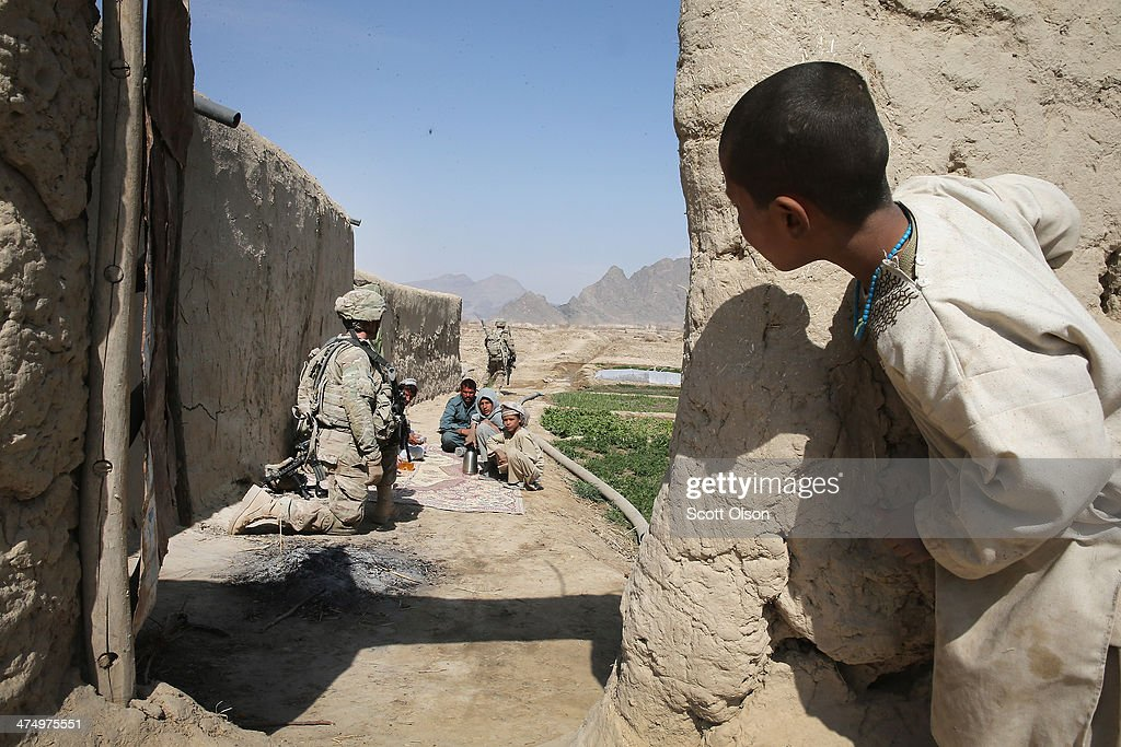 A young boy watches as soldiers from the U.S. Army's 4th squadron 2d Cavalry Regiment pause while patroling through his village on February 26, 2014 near Kandahar, Afghanistan. Defense Secretary Chuck Hagel announced he is making preparations for a complete military withdrawl from Afghanistan because Afghanistan President Hamid Karzai continues to refuse to sign the Bilateral Security Agreement. Fourth squadron 2d Cavalry Regiment is responsible for defending Kandahar Airfield against rocket attacks from insurgents.