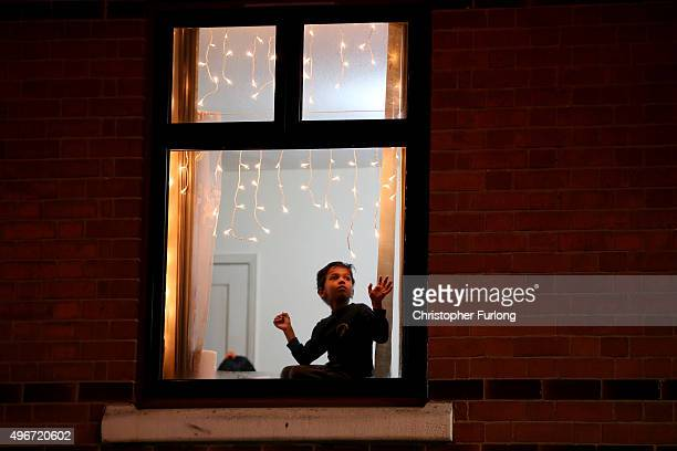 A young boy watches fireworks from his bedroom window as people gather to celebrate the Hindu festival of Diwali on November 11 2015 in Leicester...