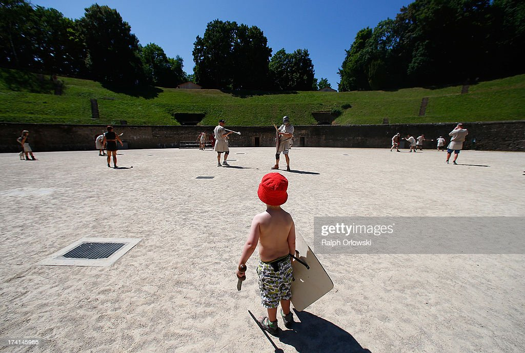 A young boy watches participants sword fighting during a one-day course at the Gladiator School in the Roman-era amphitheater on July 20, 2013 in Trier, Germany. The Gladiator School, launched by German actor Jan Krueger in 2011, seeks to teach not only the fighting skills of the gladiators of ancient Rome, but also the philosophy behind the gladiator ethos. The school offers a variety of classes, including one and three-day courses.