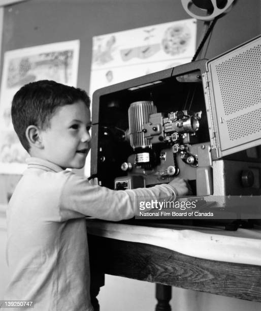A young boy watches the film projected by the movie projector that he is operating in a classroom of the Lorne Elementary School in...