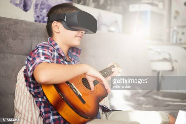 A young boy watching the virtual reality with playing guitar