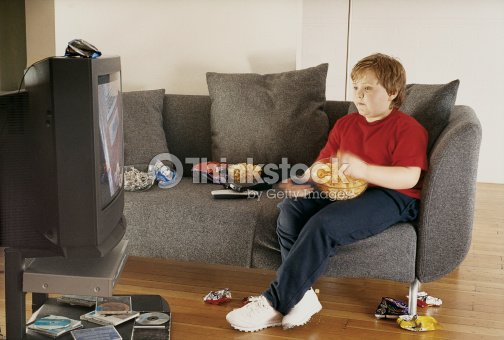 young boy watching tv on a sofa and eating crisps from a bowl