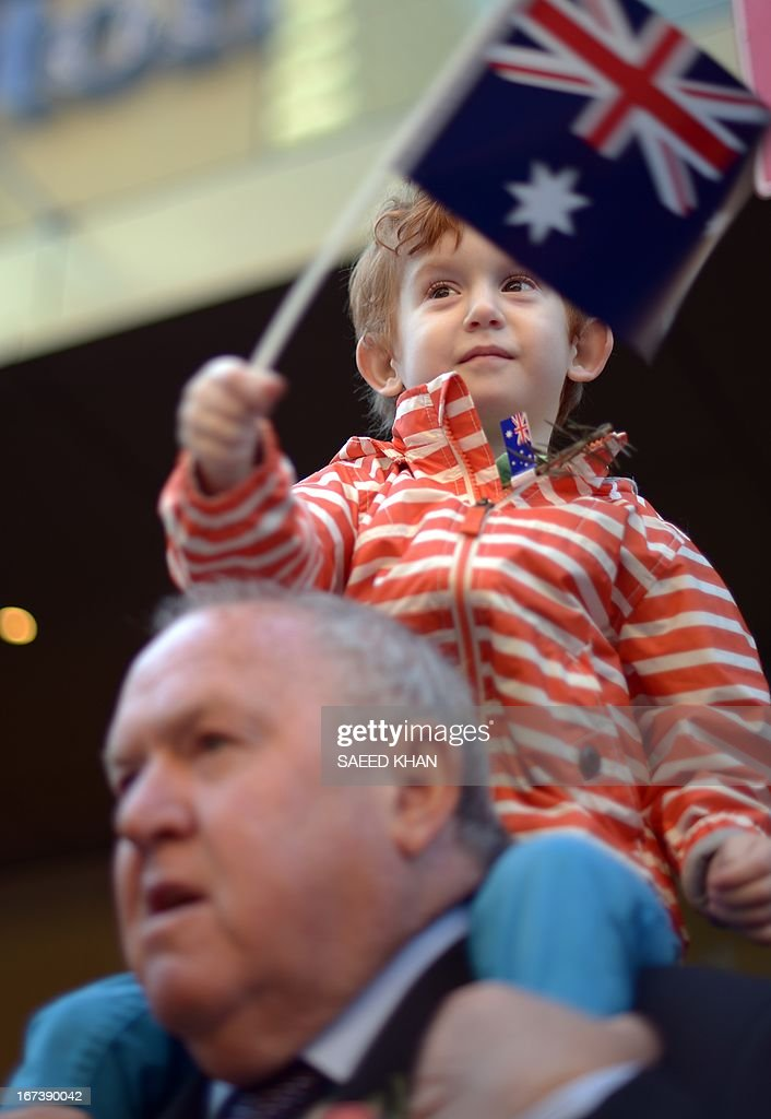 A young boy waves a flag during the Anzac Day march in Sydney on April 25, 2013. Tens of thousands of Australians and New Zealanders turned out on April 25 to honour their war dead, with moving tributes to fallen mates and calls not to forget those injured in conflict. AFP PHOTO / Saeed Khan