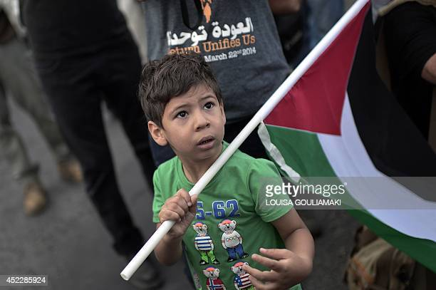 A young boy waves a Palestinian flag during a demonstration against the Israeli air strikes on Gaza outside the Israeli embassy of Athens on July 17...