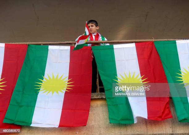 A young boy waves the Kurdish flag during celebrations in solidarity with the Kurdish Peshmerga forces at a school in the disputed northern Iraqi...