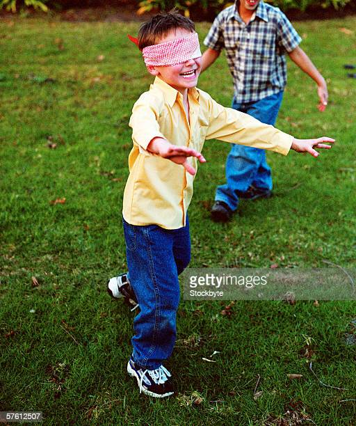 Young boy (4-8) wearing a blindfold playing with friends
