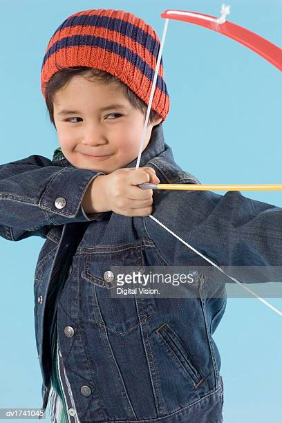 Young Boy Wearing a Denim Jacket and a Beanie Hat Playing With a Bow and Arrow