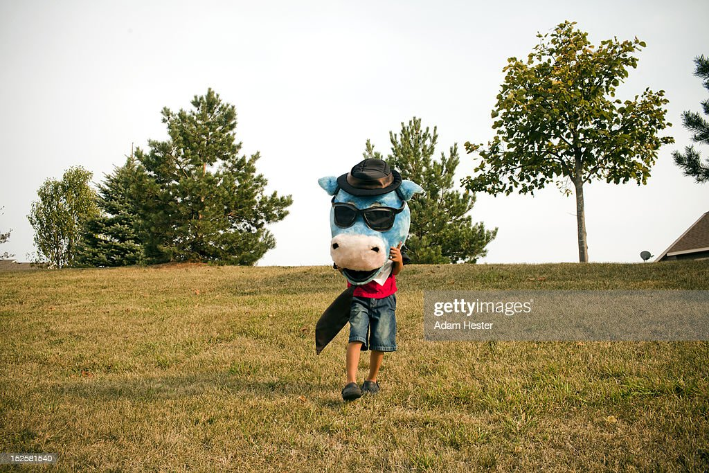 A young boy wearing a fake cow head outside. : Stock Photo