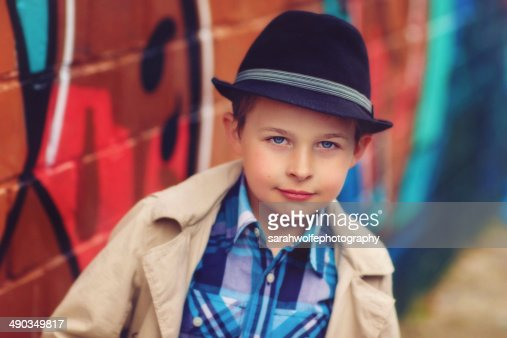 young boy wearing a fedora hat in the city
