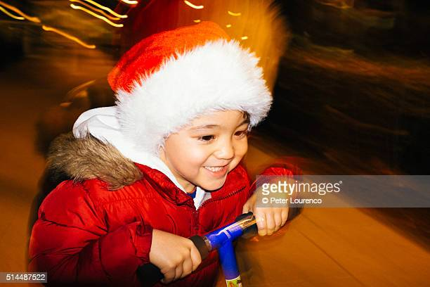 Young boy wearing a festive hat, riding a scooter