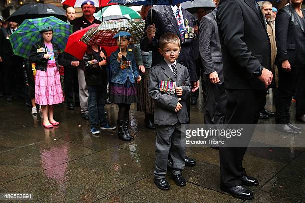 A young boy wearing a relatives medals works past the Cenotaph in Martin Place during the ANZAC Day parade on April 25 2014 in Sydney Australia...