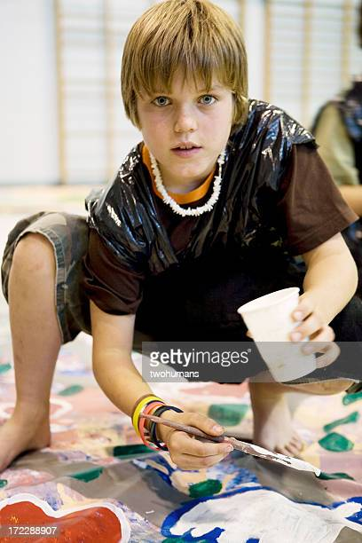 Young boy wearing a trash bag smock and painting a banner