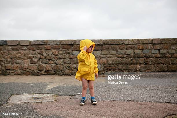 Young boy wearing a yellow jacket at the beach