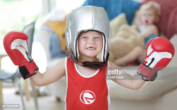 Young boy wearing boxing clothes, baby sister shouting at him from sofa