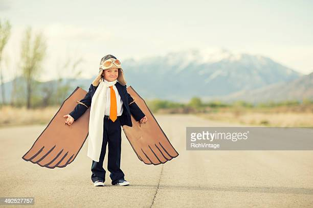 Young Boy wearing Business Suit and Cardboard Wings