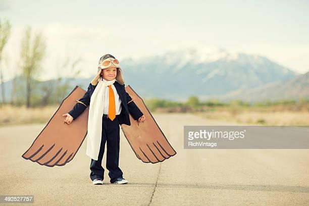 Jeune garçon portant costume d'affaires et en carton ailes