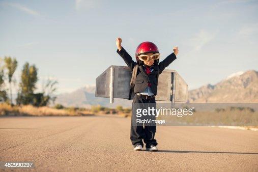 Young Boy 着のビジネススーツとジェットパックが飛ぶ