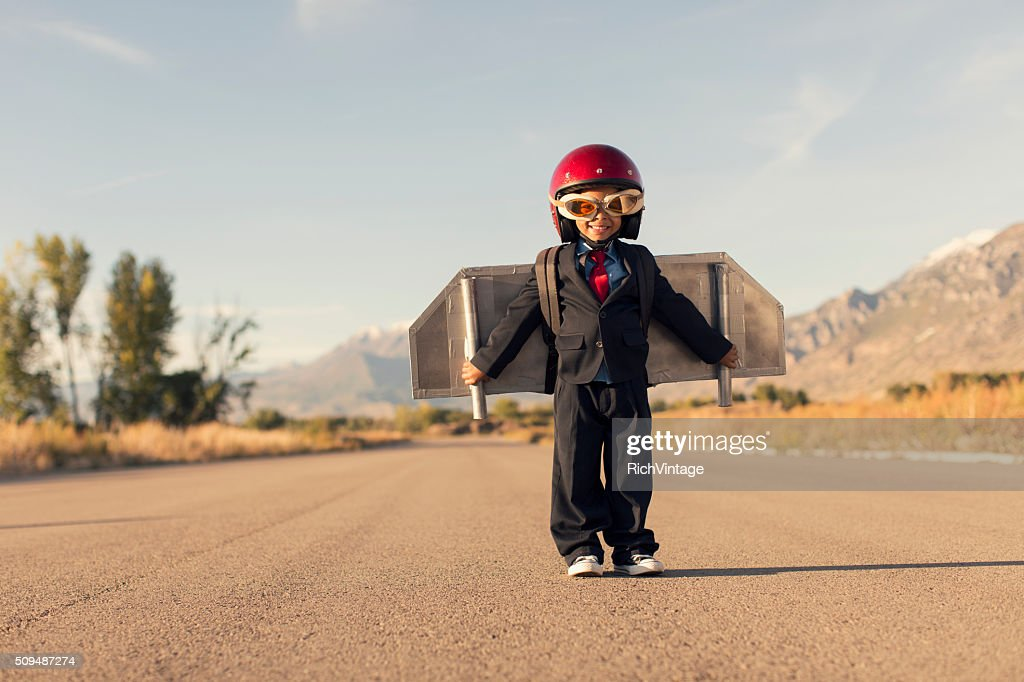 Young Boy Wearing Business Suit and Jet Pack Flies : Stock Photo