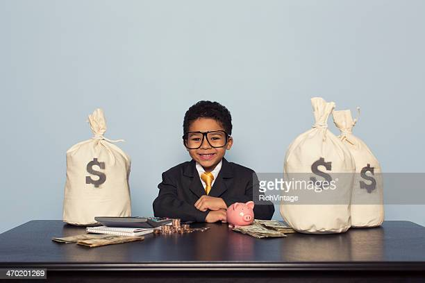 Young Boy Wearing Business Suit Sits with Money Bags