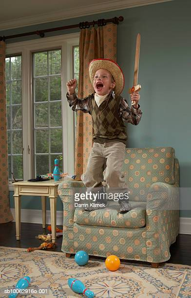 Young boy (6-7 years) wearing cowboy costume, standing on armchair yelling