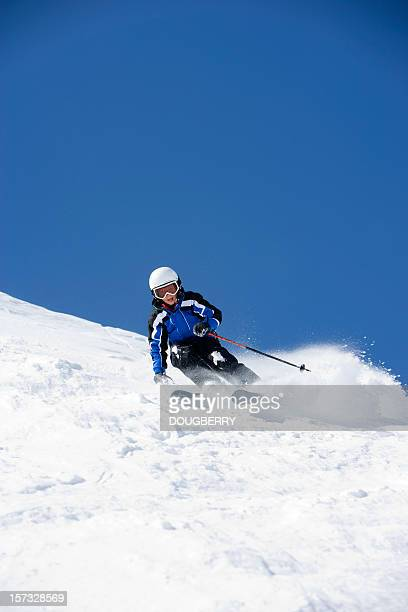 Young Boy wearing helmet while snow skiing