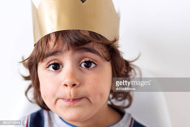 Young boy wearing paper crown