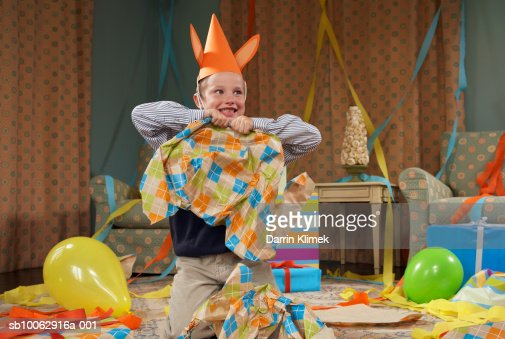 Young boy (6-7) wearing party hat, making mess in room after party : Foto de stock