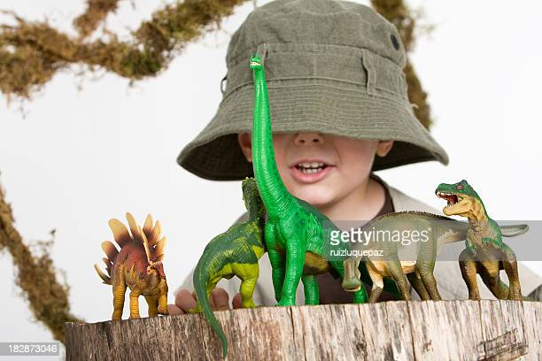 Young boy wearing safari outfit playing with toy dinosaurs