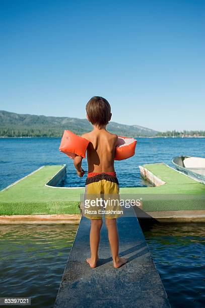 Young boy wearing water wings contemplates lake