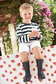 Young Boy Wearing Wellington Boots Drinking Milkshake