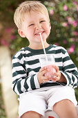 Young Boy Wearing Wellington Boots Drinking Milkshake