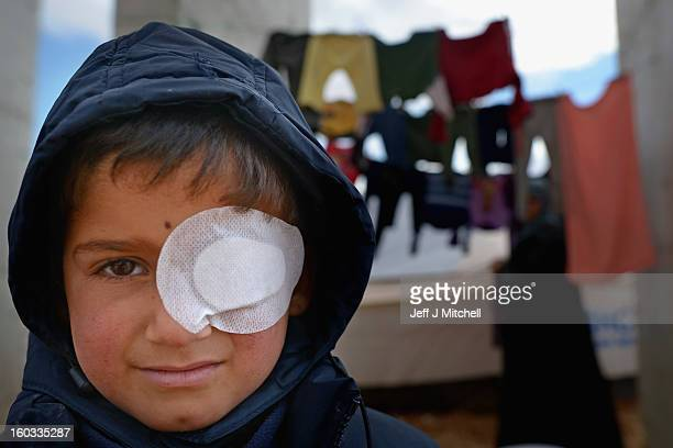 A young boy wears and eye patch as Syrian refugees go about their daily business in the Za'atari refugee camp on January 29 2013 in Mafraq Jordan...