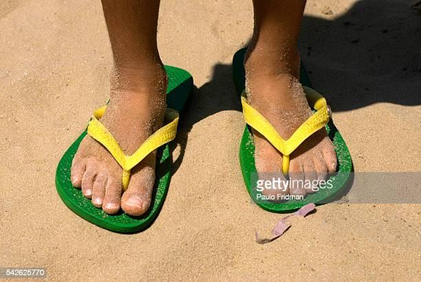 A young boy wears green and yellow Havaianas at the beach in Leblon Rio de Janeiro